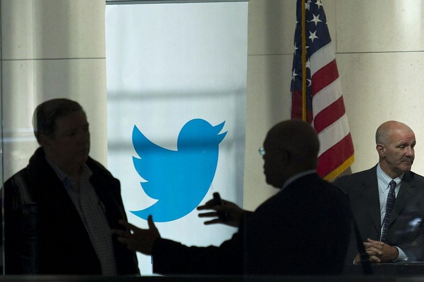 People talk inside JP Morgan headquarters near a Twitter banner, before the firm's IPO in New York, on Oct 25, 2013. Twitter Inc IPO-TWTR.N has set a relatively modest price range for its closely watched initial public offering, but some financi