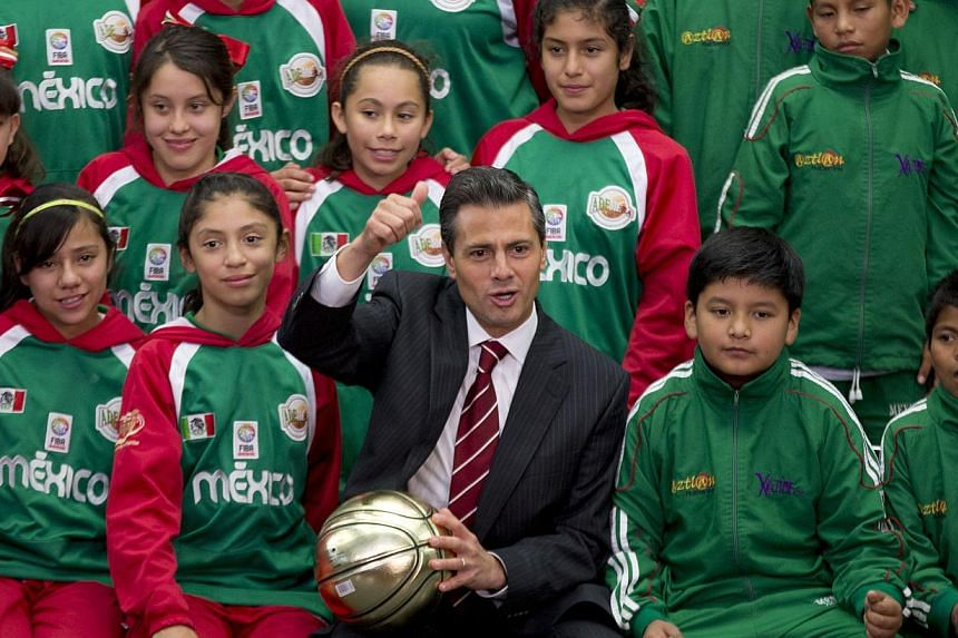 Mexico's President Enrique Pena Nieto poses for photos with young members of the Triqui Indian boys basketball team from Oaxaca, and girls basketball team from Puebla, at Los Pinos presidential residence in Mexico City, on Oct 25, 2013.Mr Pena