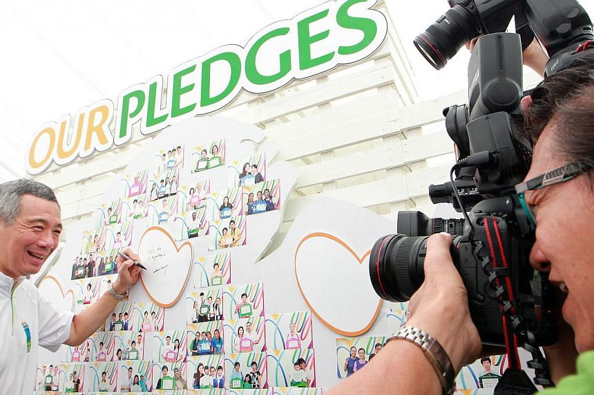 Prime Minister Lee Hsien Loong (left) poses for the cameras at the pledge board after he officially launches the Clean and Green Campaign 2014 on Oct 26, 2013. -- ST PHOTO: NEO XIAOBIN