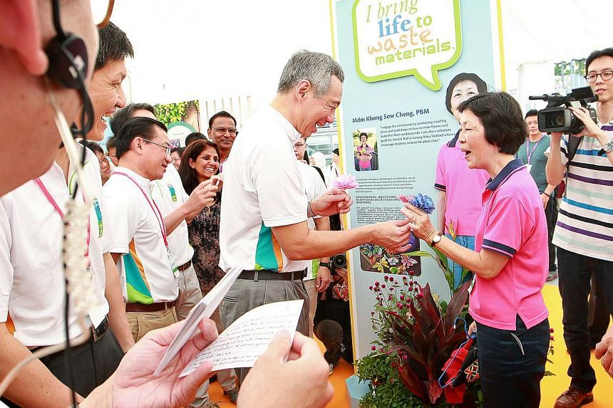 Prime Minister Lee Hsien Loong (centre, in white) receives a flower from one of the environment ambassadors Madam Khong Sow Cheng (in pink) as he tours the carnival after officially launching the Clean and Green Campaign 2014 on Oct 26, 2013. -- ST P