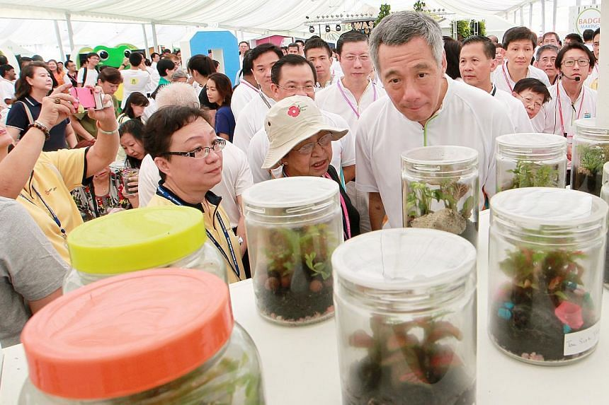 Prime Minister Lee Hsien Loong (right) looks at the bottle gardens created during Braddell Heights Eco Workshops after he launches the Clean and Green Campaign 2014 on Oct 26, 2013. -- ST PHOTO: NEO XIAOBIN