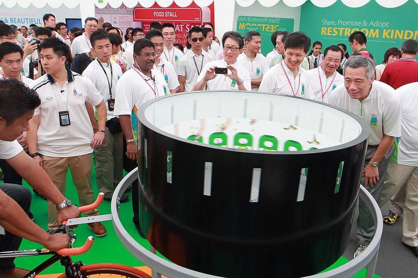 Prime Minister Lee Hsien Loong (second from right) checks out one of the interactive games at the carnival after he officially launches the Clean and Green Campaign 2014 on Oct 26, 2013. -- ST PHOTO: NEO XIAOBIN