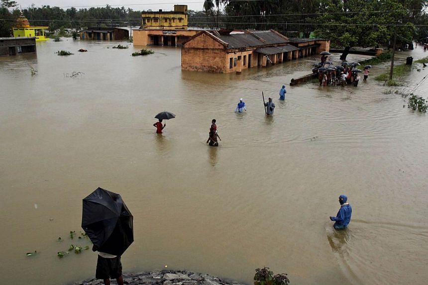 Villagers wading through floodwaters in Banapur village, in Khurda district, in the eastern Indian state of Orissa, on Friday, Oct 25, 2013. Fresh floods have killed at least 18 people in the same part of eastern India that this month saw the worst c