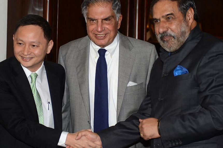 Singapore Airlines CEO Goh Choon Phong (left) shaking hands with Indian Minister for Commerce and Industry Anand Sharma (right) as Tata Group chief Ratan Tata (centre) looks on during a meeting in New Delhi on Oct 25, 2013. India's foreign investment