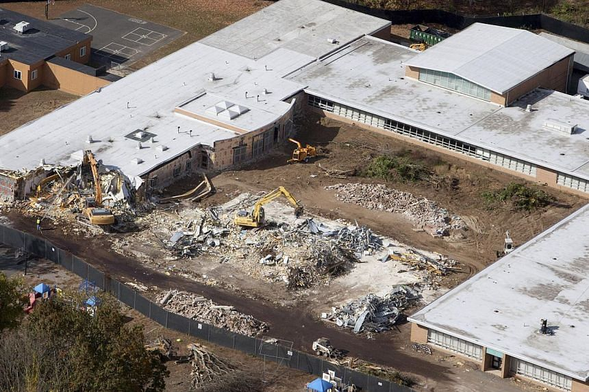 Demolition work is underway at Sandy Hook Elementary School in Newtown, Connecticut on Oct 25, 2013. Demolition work has begun on a US elementary school where 20 children and six adults were killed during a massacre last December, an official said on