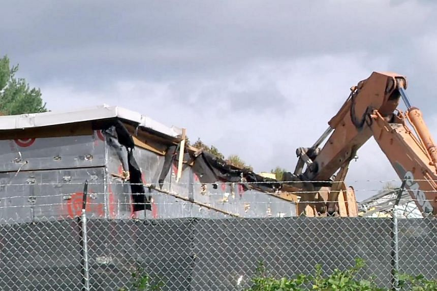 In this image taken from video, a backhoe rips into the roof of the Sandy Hook Elementary School building in Newtown, Connecticut, as demolition began on the building, on Oct. 25, 2013. Demolition work has begun on a US elementary school where 20 chi