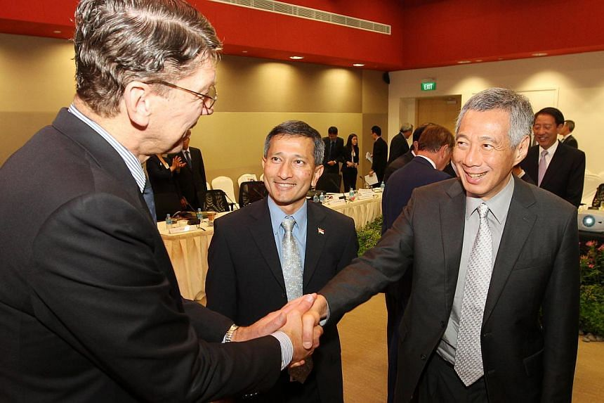 PM Lee Hsien Loong greets (left) Prof Clayton M Christensen as Dr Vivian Balakrishnan (centre) looks on, after the 7th Research, Innovation and Enterprise Council (RIEC) meeting at Create tower in UTown. PM Lee said The Returning Singaporean Sci