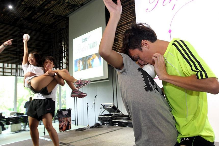 Mr Nicolas Amet, 24, and Miss Victoria Hoo, 23, try to move a coconut-sized ball from their bellies to their lips in the last challenge at the finale of Kiss92's Perfect Match conteston Saturday, Oct 26, 2013. -- ST PHOTO:SEAH KWANG PENG