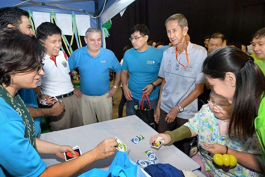 Minister for Social and Family DevelopmentChan Chun Sing (in white), Standard Chartered Singapore CEO Ray Ferguson and the bank's volunteers at a game stall at the 'Silver Lining' carnival. -- PHOTO: STANDARD CHARTERED