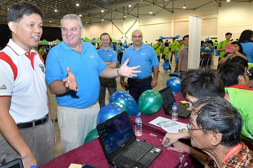 (From left) Minister for Social and Family DevelopmentChan Chun Sing, Standard Chartered Singapore CEO Ray Ferguson and the bank's volunteers at the 'computer zone' booth at the first 'Silver Lining' carnival, held on Saturday, Oct 26, 20