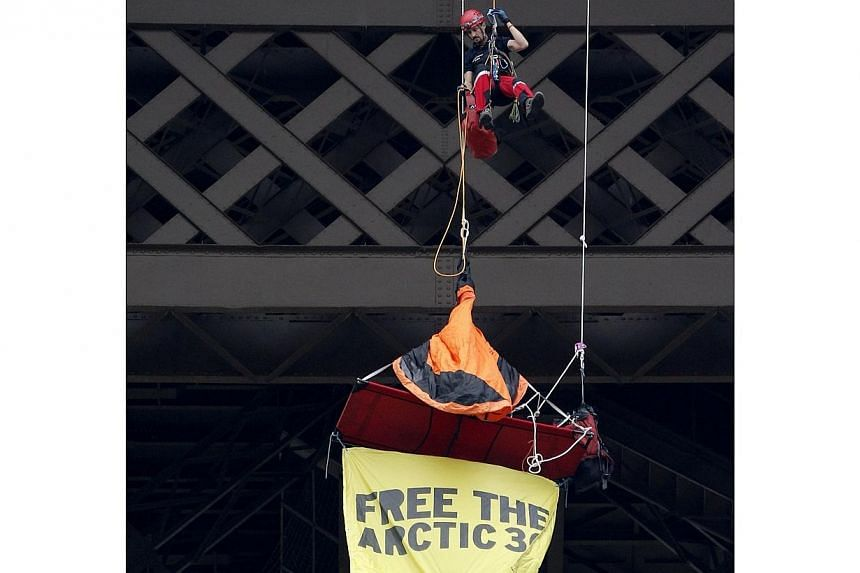 A French firefighter (above) speaking with the Greenpeace activist hanging from the second floor of the Eiffel Tower in Paris, on Saturday, Oct 26, 2013.-- PHOTO: AP