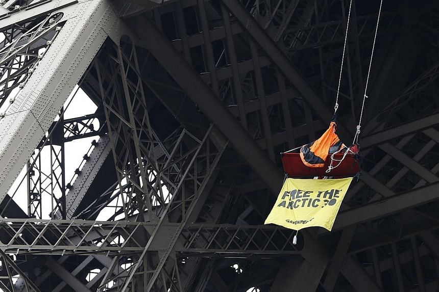 A Greenpeace activist on Saturday staged a protest in a tent suspended from the second floor of the Eiffel Tower against Russia's detention of 30 members of the environmental lobby group. -- PHOTO: AFP