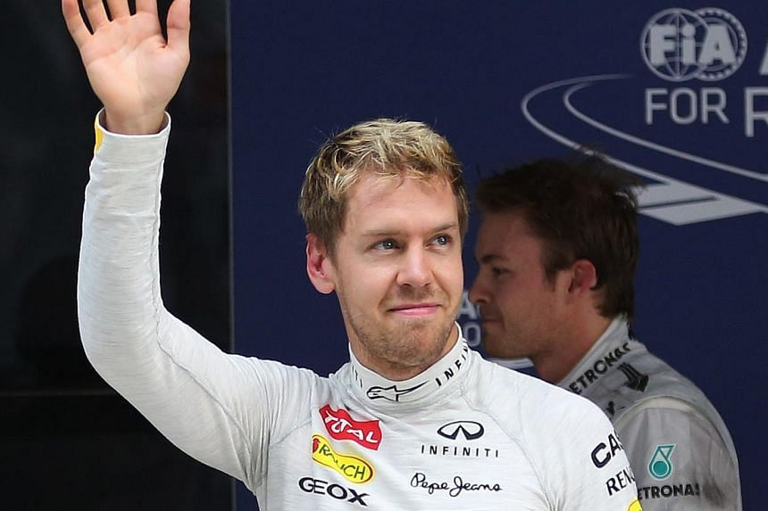 Red Bull driver Sebastian Vettel of Germany waves to the crowd after winning the qualifying session at the Indian Formula One Grand Prix at the Buddh International Circuit in Noida, India, on Saturday, Oct 26, 2013. -- PHOTO: AP