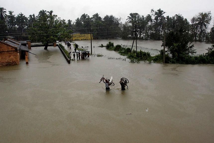 Two villagers carry their bicycles and wade through floodwaters in Banapur village, in Khurda district, in the eastern Indian state of Orissa, on Friday, Oct 25, 2013. -- PHOTO: AP