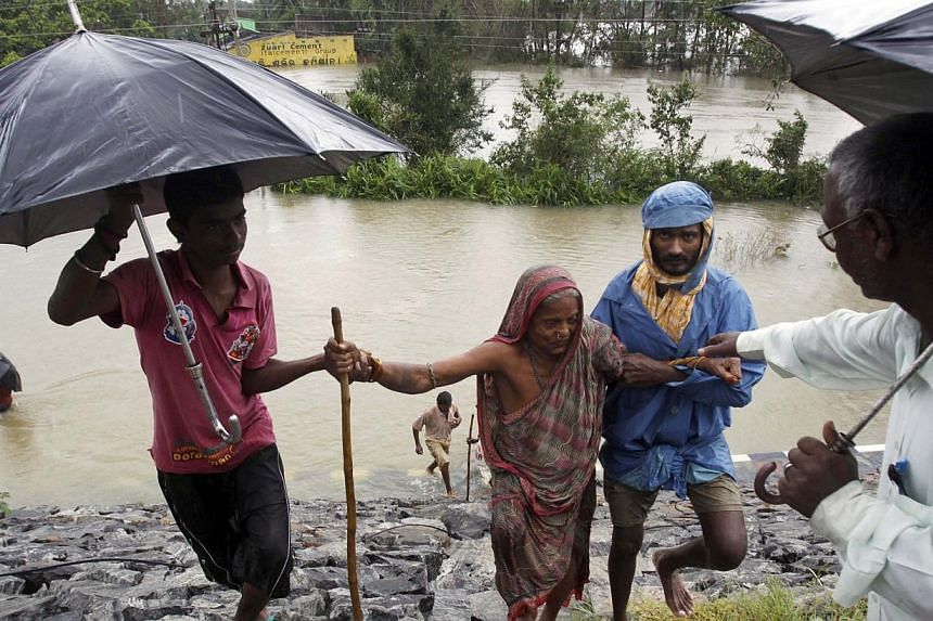 Indian villagers help an elderly woman to safer ground after crossing floodwaters in Khurda district, in the eastern Indian state of Orissa, on Friday, Oct 25, 2013. -- PHOTO: AP