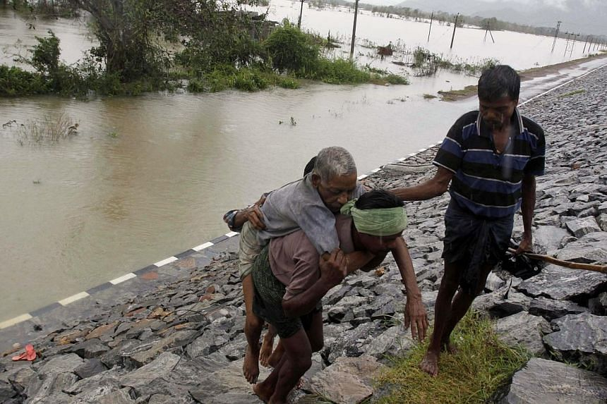 An Indian villager carries an elderly man to safety after crossing floodwaters in Khurda district, in the eastern Indian state of Orissa, on Friday, Oct 25, 2013. -- PHOTO: AP