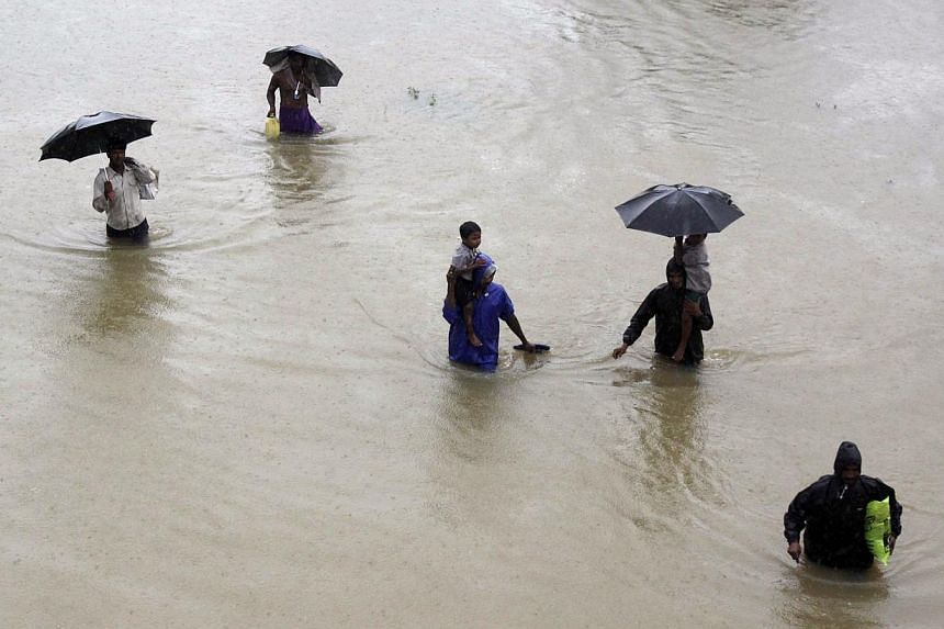 Villagers wade through floodwaters to reach safer areas in Khurda district, in the eastern Indian state of Orissa, on Friday, Oct 25, 2013. -- PHOTO: AP