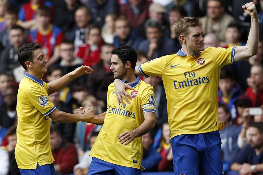 Arsenal's Mikel Arteta (centre) celebrates his penalty against Crystal Palace with teammates Mesut Oezil (left) and Per Mertesacker during their English Premier League match at Selhurst Park on Saturday, Oct 26, 2013. Arteta scored and was then