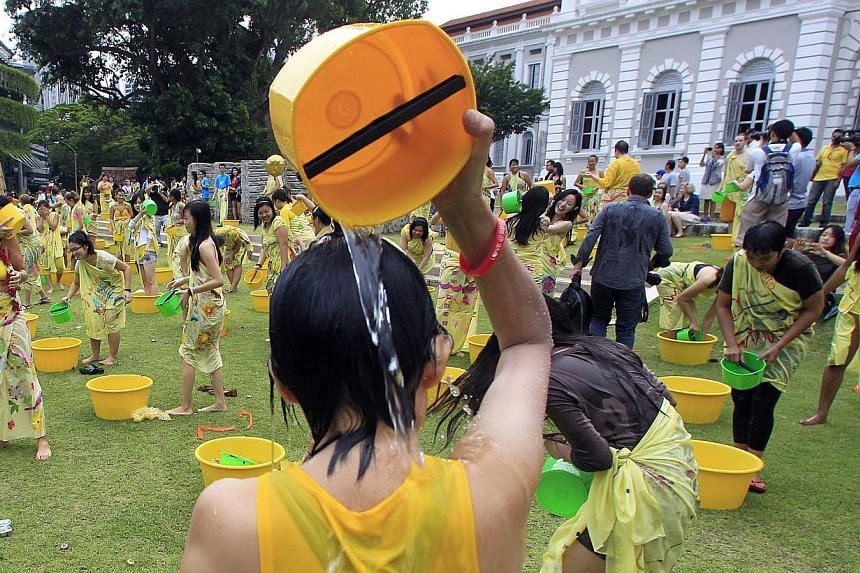 Participants (left) having fun on the lawn of the National Museum yesterday while taking part in a mass Mandi Bunga or flower bath. The performance art piece by Malaysian artist Sharon Chin (above, holding up flag) was one of 10 community-driven arts