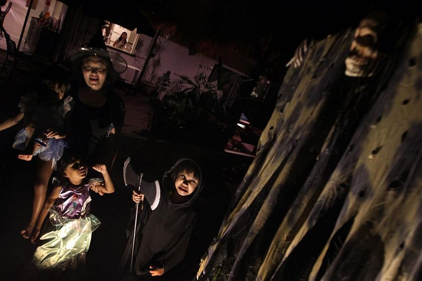Ghouls' night out: Mrs Patricia J. Raj with her twin three-year-old daughters Fonseka Mikaela Jesslyn (left) and Fonseka Alysandra Domigue (second from left), and Mr Isaac Thomas Raj's five-year-old daughter Valerie Eden Thomas, in the garden of