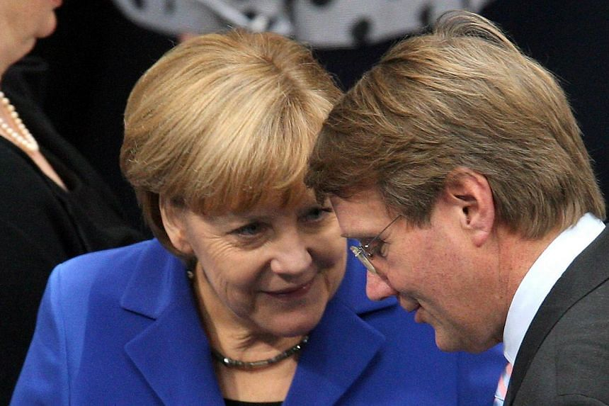 This picture taken on Oct 22, 2013 in Berlin shows German Chancellor Angela Merkel (left) talk with Chief of Staff Ronald Pofalla (right) during the election of the Bundestag President at the constitutive meeting at the Bundestag (lower house of parl