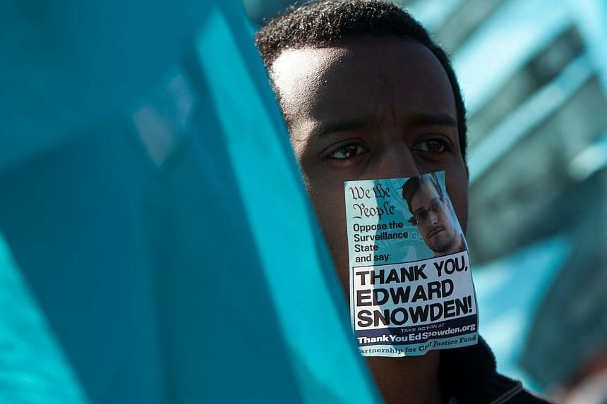 A protester wearing a sticker over his mouth featuring former National Security Agency employee Edward Snowden, listens to speakers during the Stop Watching Us Rally protesting surveillance by the US National Security Agency, on Oct 26, 2013, in fron