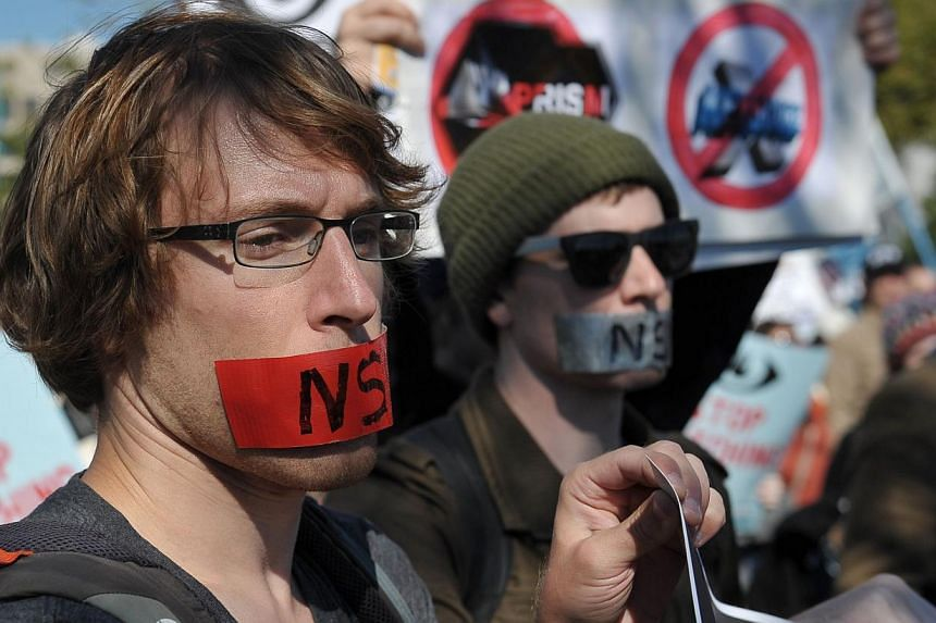 Demonstrators hold placards and banners during a protest against government surveillance on Oct 26, 2013 in Washington, DC. -- PHOTO: AFP