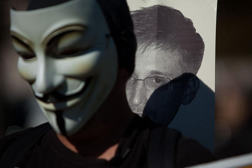 A protester wearing the mask often seen during the Occupy protests, marches with a sign featuring the likeness of former National Security Agency employee Edward Snowden during the Stop Watching Us Rally protesting surveillance by the US National Sec