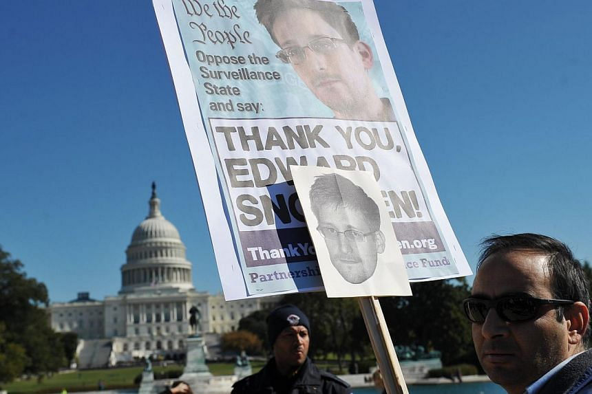 Demonstrators hold placards supporting former US intelligence analyst Edward Snowden during a protest against government surveillance on Oct 26, 2013 in Washington, DC. -- PHOTO: AFP