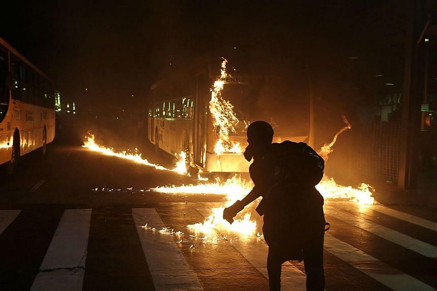 A demonstrator from the Black Bloc anarchist group throws a Molotov cocktail at a burning bus during a protest against Sao Paulo's Governor Geraldo Alckmin in Sao Paulo, Brazil, Friday, Oct. 25, 2013.Protesters went on a rampage in Brazil's lar