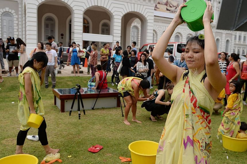 ST reporter Lisabel Ting (right) taking part in Mandi Bunga (Flower Bath) which is part of this year's Singapore Biennale. -- ST PHOTO: RAJ NADARAJAN