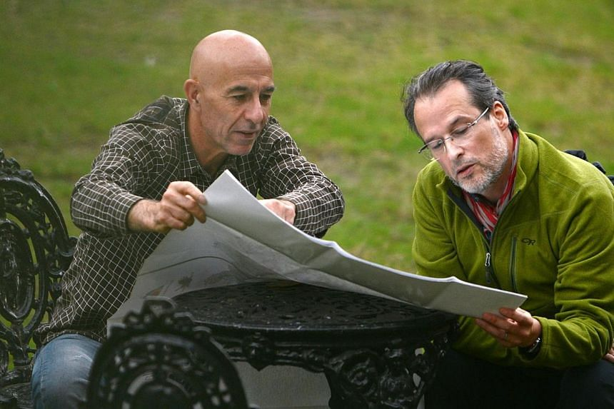 French multiple sclerosis sufferer MrMarc Kopp (right) and tandem skydiving partner Mr Mario Gervasi (left) looks at a map of Nepal in Kathmandu, on Oct 22, 2013. -- FILE PHOTO: AFP