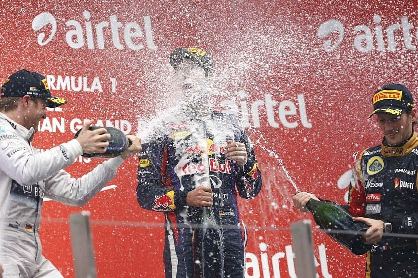Mercedes driver Nico Rosberg of Germany (left) and Lotus driver Romain Grosjean (right) of France spray champagne on the face of Red Bull driver Sebastian Vettel of Germany on the podiumafter theFormula One Indian Grand Prix 2013 at the B