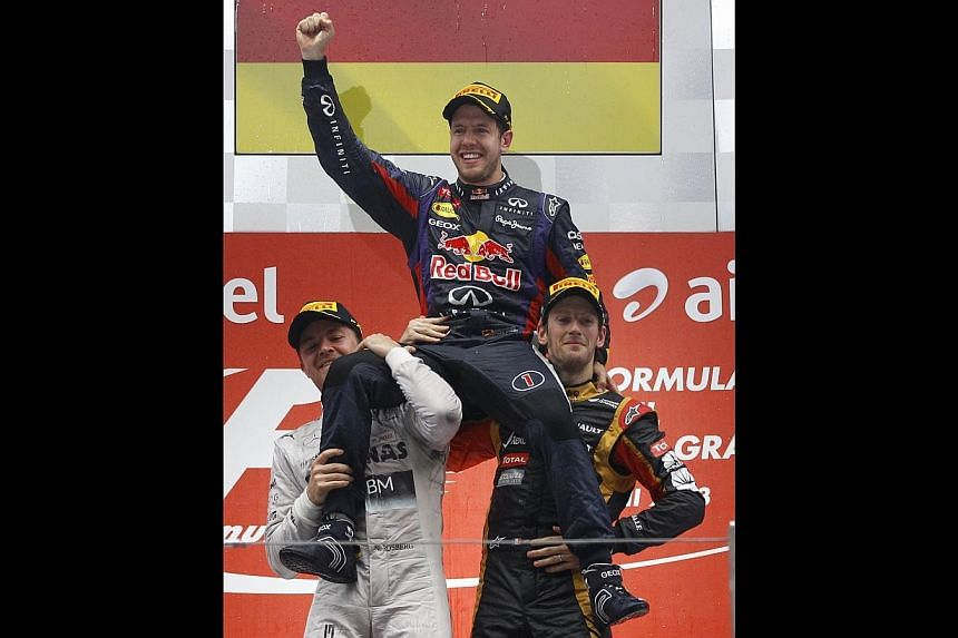 Red Bull driver Sebastian Vettel of Germany (centre) is hoisted by Mercedes driver Nico Rosberg (left) of Germany and Lotus driver Romain Grosjean of France as they celebrate on the podiumafter theFormula One Indian Grand Prix 2013 at the