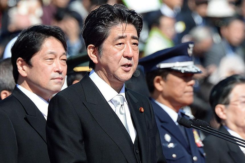 Japanese Prime Minister Shinzo Abe (centre) delivers a speech beside Defence Minister Itsunori Onodera (left) during the military review at the Ground Self-Defence Force's Asaka training ground on Sunday, Oct 27, 2013.Mr Abe warned China on Sun