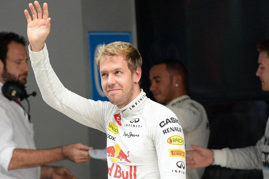 Red Bull driver Sebastian Vettel of Germany waves to the crowd after qualifying first for pole position for the Formula One India Grand Prix at The Buddh International circuit in Greater Noida on the outskirts of New Delhi on Oct 26, 2013, ahead of t