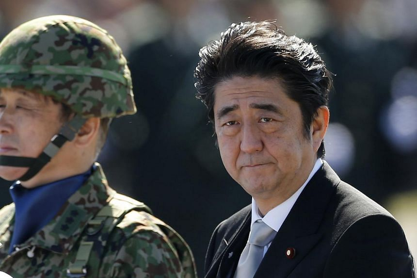 Japanese Prime Minister Shinzo Abe reviewing the Japan Self-Defence Forces' (SDF) troops during the annual SDF ceremony at Asaka Base in Asaka, near Tokyo on October 27, 2013. -- FILE PHOTO: REUTERS