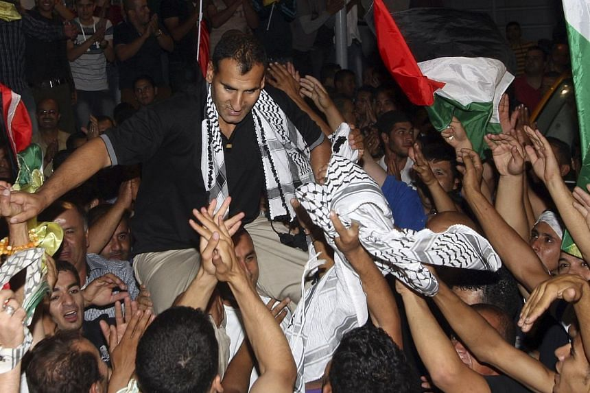 Freed Palestinian prisoner Hosni Sawalha (centre) is greeted by relatives and friends upon his arrival in the West Bank village of Azmout near Nablus early August 14, 2013.Israel on Sunday approved the release of 26 Palestinian prisoners,