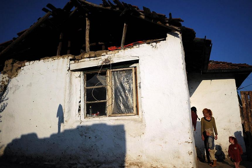 A picture taken on October 24, 2013, shows three of the children of Sasha Ruseva and Atanas Rusev in front of their home in the Roma district of the central Bulgarian town of Nikolaevo.The Bulgarian Roma mother of Maria, a young blonde girl who