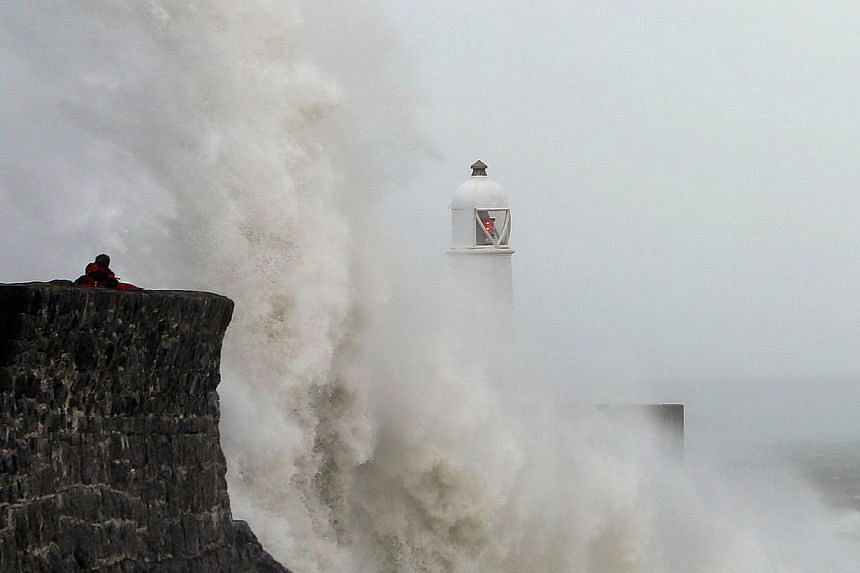 Waves crash against the sea barriers in Porthcawl, south Wales on October 27, 2013 ahead of the arrival of a predicted storm.Britain was braced on Sunday for its worst storm in a decade, with heavy rain and winds of more than 130kmh set t