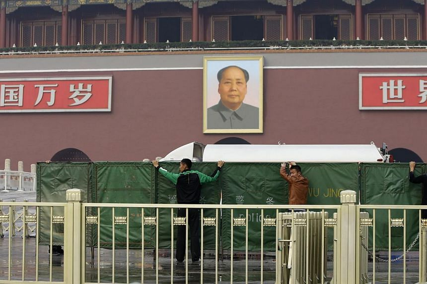 Policemen set up barriers in front of the giant portrait of the late Chinese chairman Mao Zedong as they clean up after a car accident in Tiananmen Square in Beijing on Monday, Oct 28, 2013. Three people were killed and many injured on Monday, police