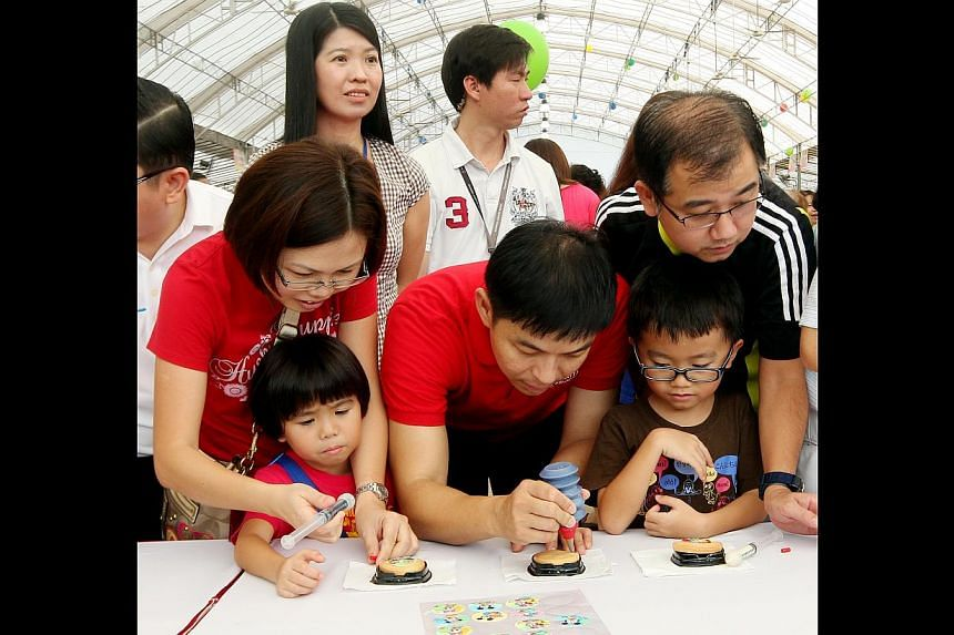 Acting Manpower Minister Tan Chuan-Jin (second from left) decorating cookies with (from left) residents Gan Kim Lee, 39, Lim Jing Xuan, five, Johnny Lim Jun Yang, seven, and Lim Seng Tiong, 40, at a carnival. -- ST PHOTO: LAU FOOK KONG