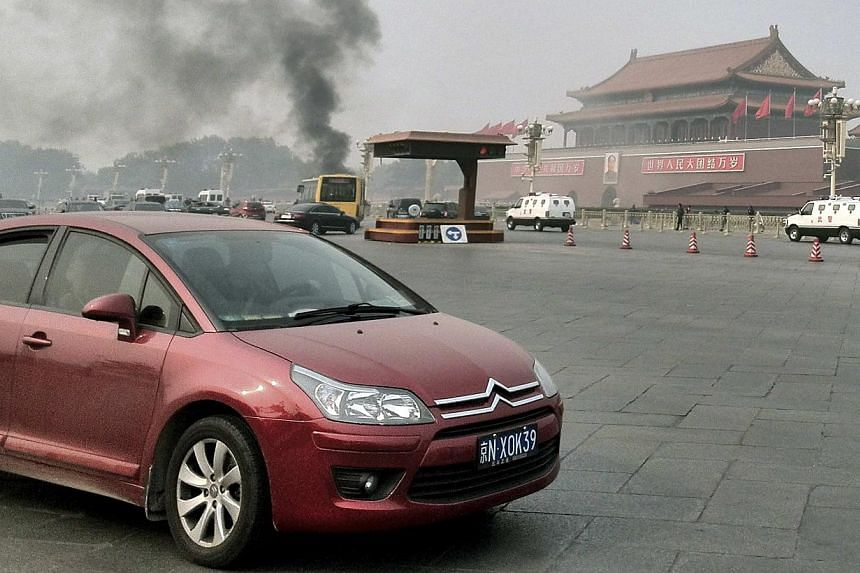 Vehicles travel along Chang'an Avenue as smoke rises in front of a portrait of late Chinese chairman Mao Zedong at Tiananmen Square in Beijing on Monday, Oct 28, 2013. Five people were killed and dozens injured on Monday, the government said, wh