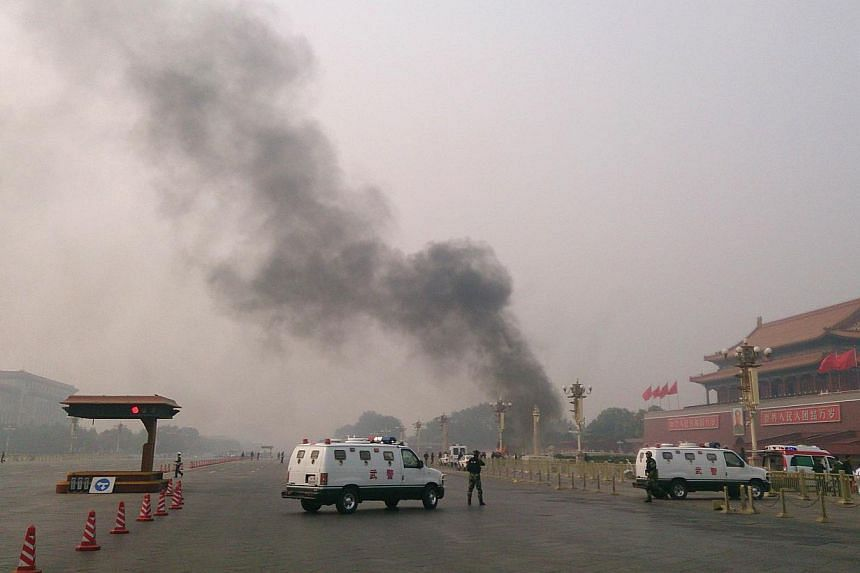 Police cars block off the roads leading into Tiananmen Square as smoke rises into the air after a vehicle crashed in front of Tiananmen Gate in Beijing on Monday, Oct 28, 2013. -- PHOTO: AFP