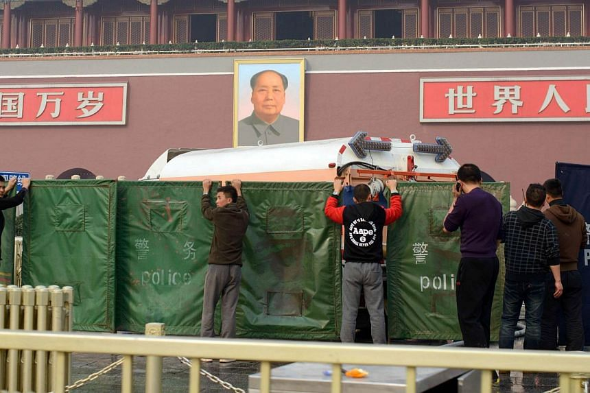 Workers stand before a police barrier outside Tiananmen Gate in Beijing on Monday, Oct 28, 2013, after a vehicle crashed near the area. -- PHOTO: AFP