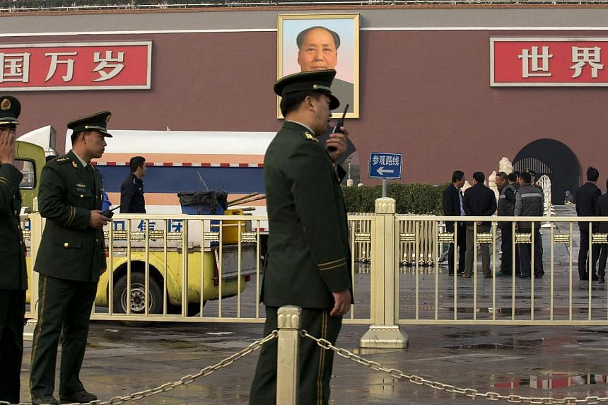 Paramilitary police officers, police officers, and cleaners work in front of Tiananmen Gate following a car fire in Beijing, China on Monday, Oct 28, 2013. -- PHOTO: AP