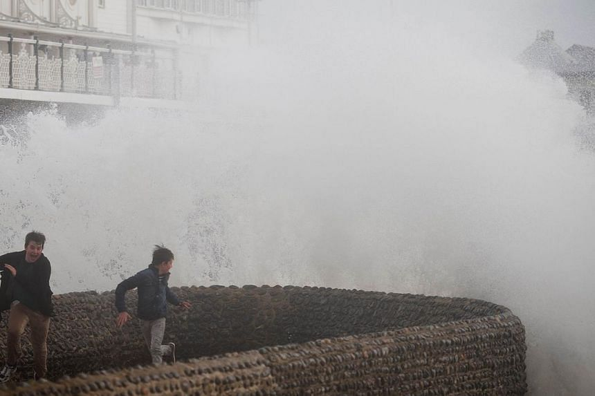 Two boys attempt to evade the spray as large waves crash against the walls of Brighton seafront, in southern England on Sunday, Oct 27, 2013.Strong storm winds and rain battered southern parts of England and Wales early on Monday, Oct 28, 2013,