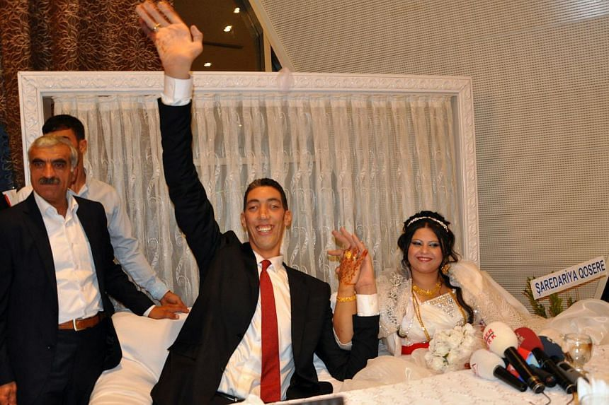 "The world's tallest man, Sultan Kosen (centre), waves on Oct 27, 2013, in Mardin during his wedding ceremony with a Syrian woman. Mr Kosen, at 2.51m the world's tallest man, has wed a Syrian woman he called the ""love of my life"", though he towers ove"