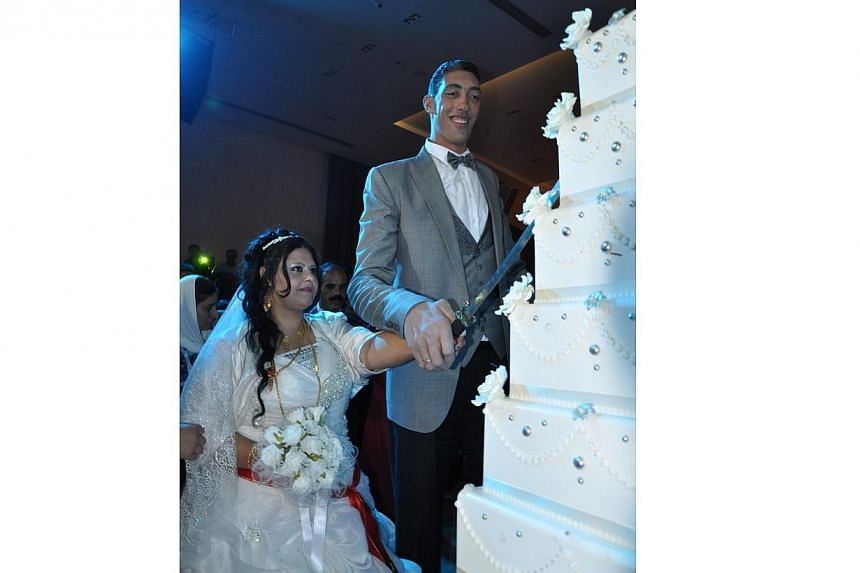 The world's tallest man Sultan Kosen (right) and his bride cut their wedding cake on Oct 27, 2013, in Mardin during their wedding ceremony. -- PHOTO: AFP