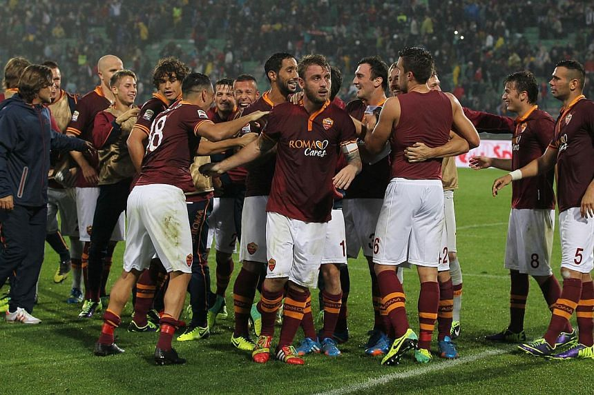 AS Roma players celebrate at the end of the Serie A soccer match between Udinese and Roma, at the Friuli Stadium in Udine, Italy, Sunday, on Oct. 27, 2013.League leaders Roma beat Udinese 1-0 away on Sunday to set a new all-time record of nine